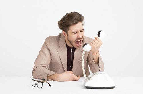 Man schreeuwt in de hoorn van een ouderwetse telefoon. Geen effectieve communicatie!